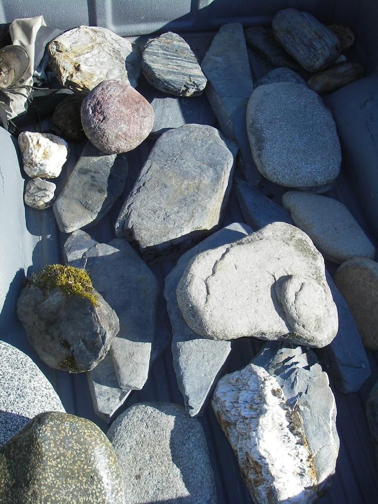 A truckload of rocks gathered along the river.